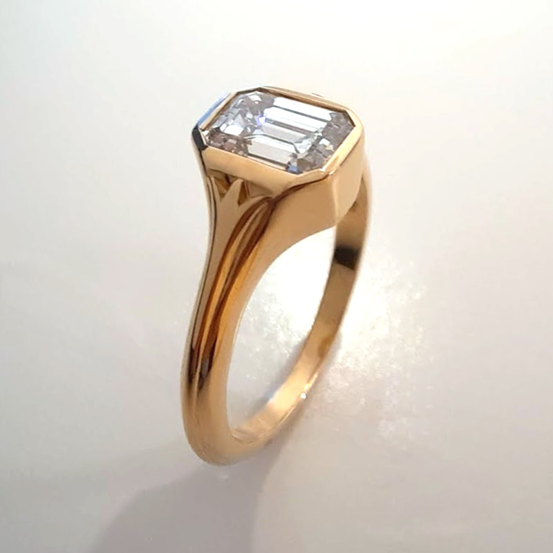 Flowers engagement ring signetring in 18K yellow gold with a stunning 0.93 ct. diamond in emerald cut and two abstract flowers on the sides Daphne Meesters Jewellery Designer Goldsmith The Hague Netherlands