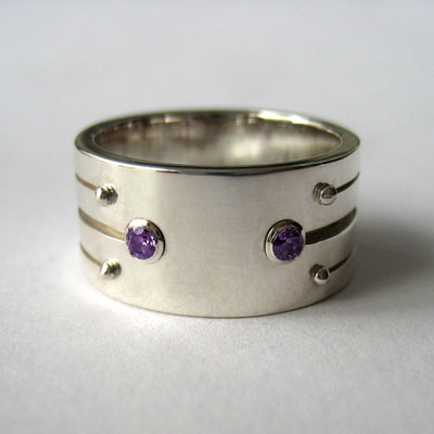 Engagement ring wide band with stripe pattern sterling silver and amethyst faceted stones Soyuz 1 love you to the moon and back say yes proposal Daphne Meesters Jewellery Designer Goldsmith The Hague Netherlands