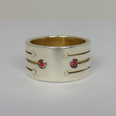 Engagement ring wide band with stripe pattern sterling silver 14K yellow gold and rubies faceted stones Soyuz 2 love you to the moon and back say yes proposal Daphne Meesters Jewellery Designer Goldsmith The Hague Netherlands