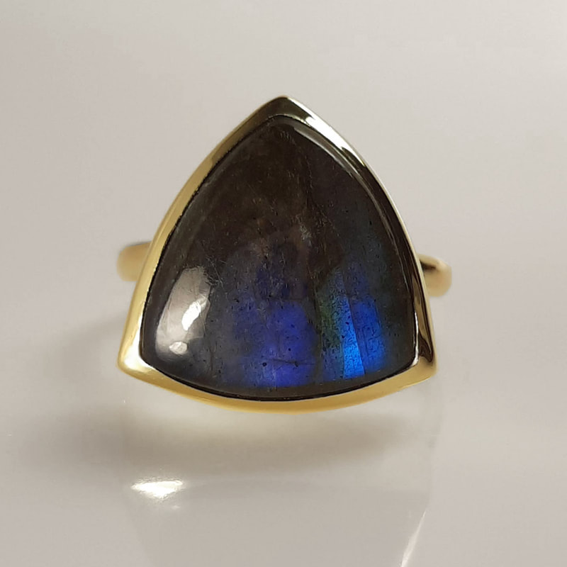 Trilliant memorial ring ashes jewellery from inherited 14K yellow gold with trilliant cut labradorite grey black with blue shine filled underneath with ashes of a deseased Daphne Meesters Jewellery Designer Goldsmith The Hague Netherlands