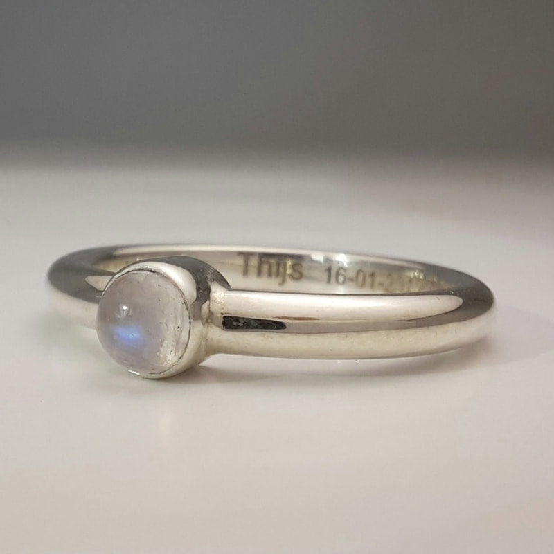 Simple delicate memorial ring with ashes of a loved one in a smal chamber underneath the moonstone Daphne Meesters Jewellery Designer Goldsmith The Hague Netherlands