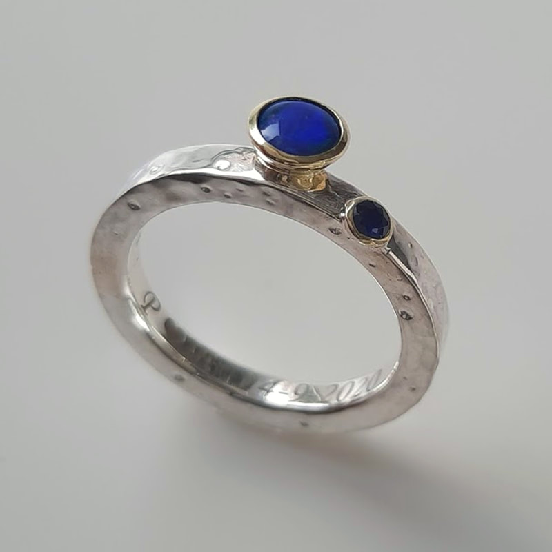 'Craters' ring with hammered moon craters surface from sterling silver and inherited 14 carat yellow gold bowls with blue green opal and dark blue sapphire  Daphne Meesters Jewellery Designer Goldsmith The Hague Netherlands