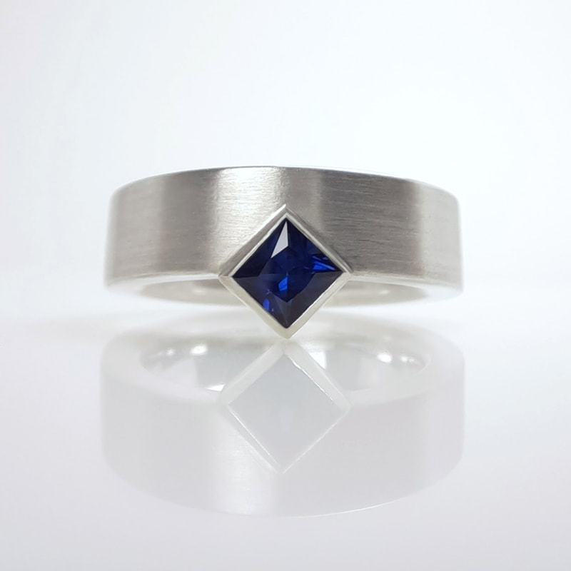 Fair and square ring  sterling silver modern wide band with matte finish and stunning dark blue sapphire princess cut square Daphne Meesters Jewellery Designer Goldsmith The Hague Netherlands