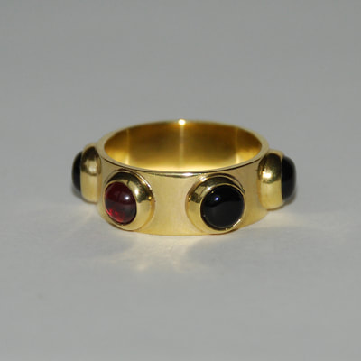 Russian roulette ring From Russia with love collection sterling silver 5 black onyx cabochons and 1 red garnet cabochon 14K gold layer size 17 or 17.5 millimeters € 236,50 per piece Daphne Meesters Jewellery Designer Goldsmith The Hague Netherlands