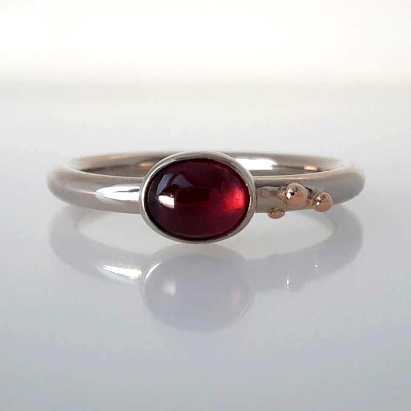 Stellina ring 14K white gold round wire ring with red gold balls and a oval spinel in a burgundy colour designer goldsmith Daphne Meesters Jewellery The Hague Netherlands