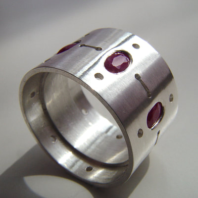Ring sterling silver and oval faceted cut rubies lines dots contemporary wide band Daphne Meesters Jewellery  Designer Goldsmith The Hague Netherlands