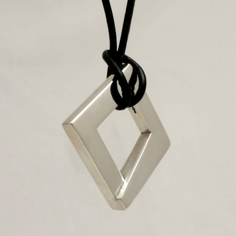 Trapezoid unisex wedding pendant alternative wedding ring band sterling silver Trapezoid square trapezoidal black surface on black leather cord shiny polish Daphne Meesters Jewellery  Designer  Goldsmith The Hague Netherlands