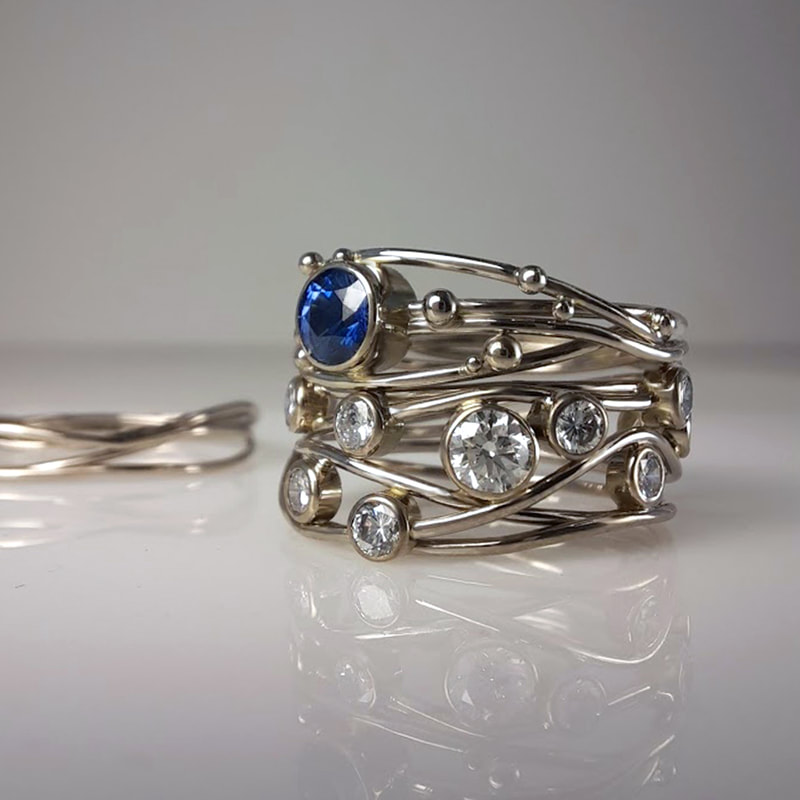 Birds nest engagement ring and wedding rings from 14 carat white gold wire and balls with sapphire and precious inherited diamonds in between  Daphne Meesters Jewellery Designer Goldsmith The Hague Netherlands